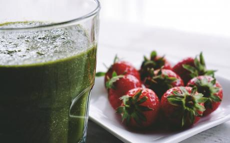 Strawberries displayed on a white plate beside a green smoothie in a tall glass