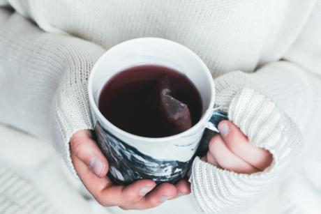 A woman holding her hands around a tea cup