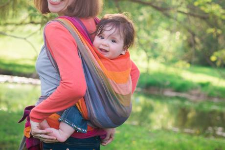 mom carrying baby in a sling on her back