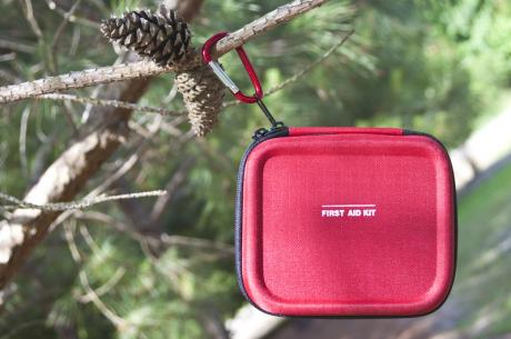 red first aid kit hanging on a tree branch