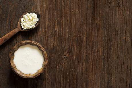 wooden bowl of kefir and wooden spoon with kefir grains on a wooden  table