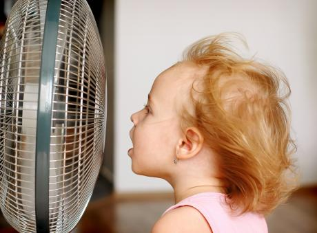 little girl keeping cool in front of an electric fan