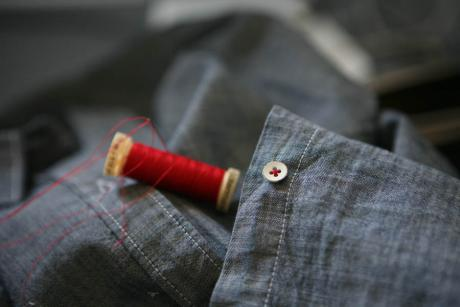 blue shirt with spool of red thread