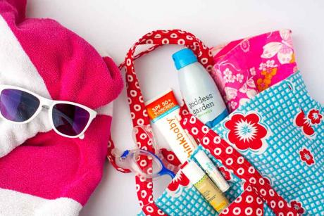 beach bag with assortment of sunny day items including sunscreen