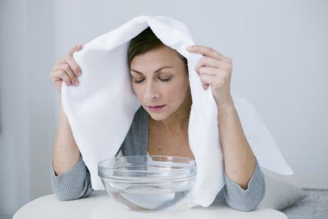 woman performing a steam inhalation over a glass bowl