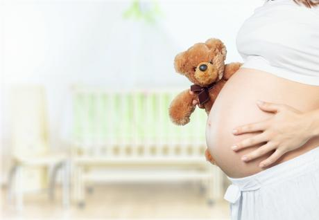 pregnant belly with woman's hand on it and teddy bear peeking out from behind