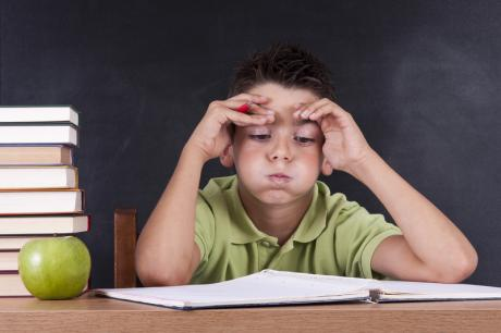 stressed out boy at school desk in green t-shirt